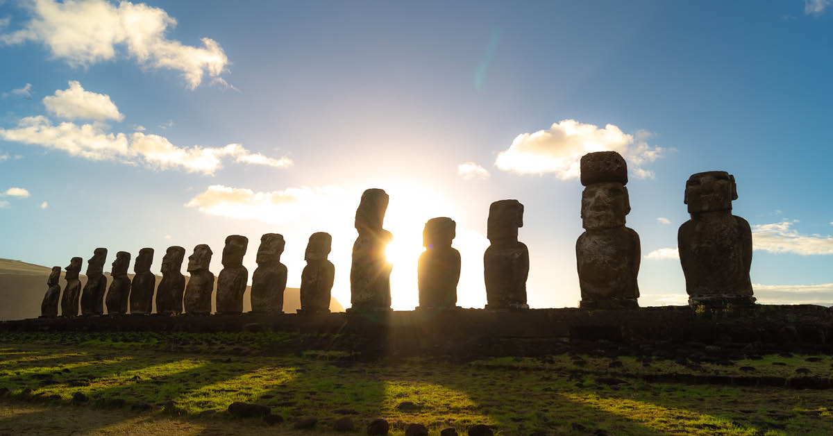 Sun setting behind a row of Easter Island Heads