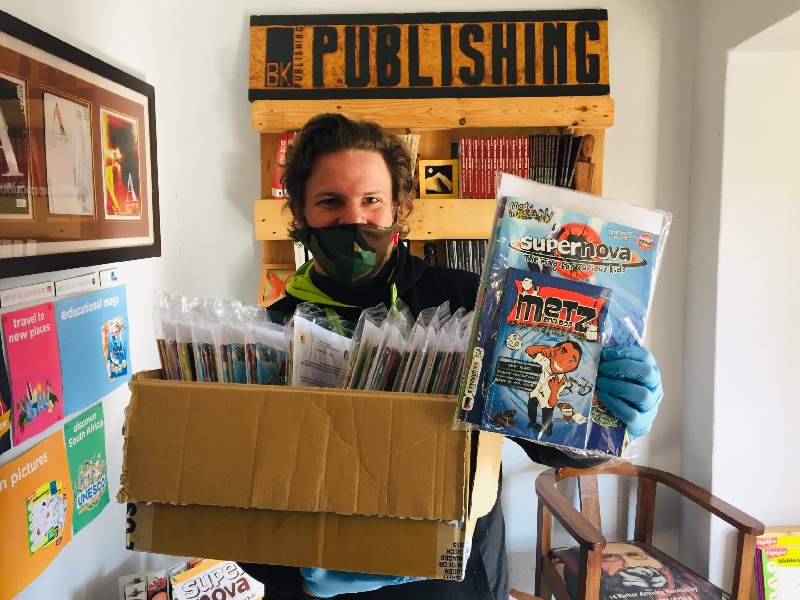 Publisher Benoit Knox holding up a box of Food for Thought magazine and book packs.